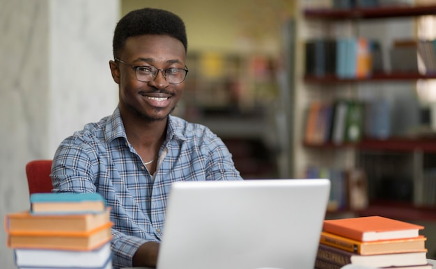 Medium shot smiley student with laptop