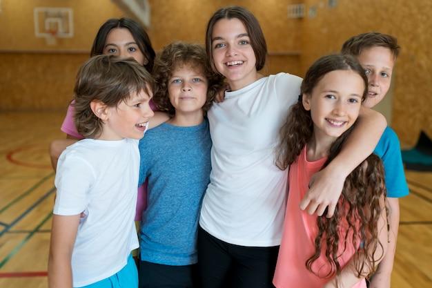 Medium shot smiley students at gym