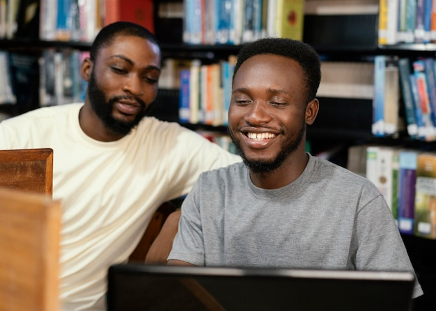 ノートパソコンでミディアムショットのスマイリー学生