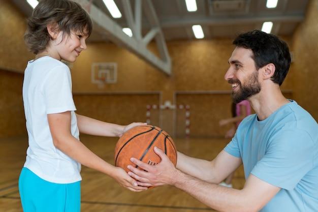 Medium shot smiley teacher and kid with basket ball