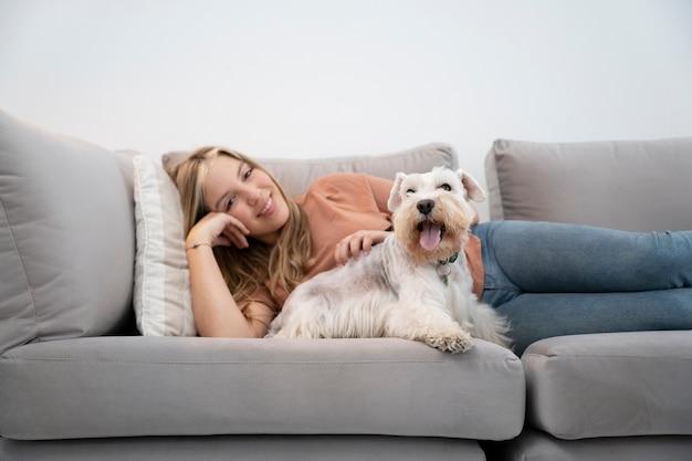 ミディアムショットの笑顔の女性とソファの上の犬