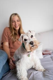 ミディアムショットのスマイリー女性と犬