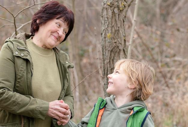 중간 샷 웃는 여자와 숲에서 아이