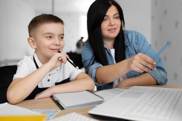 Улыбающаяся женщина среднего выстрела и ребенок с ноутбуком