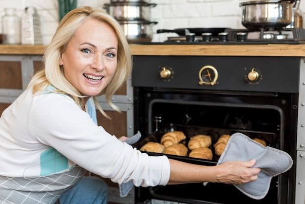 Medium shot smiley woman baking croissants