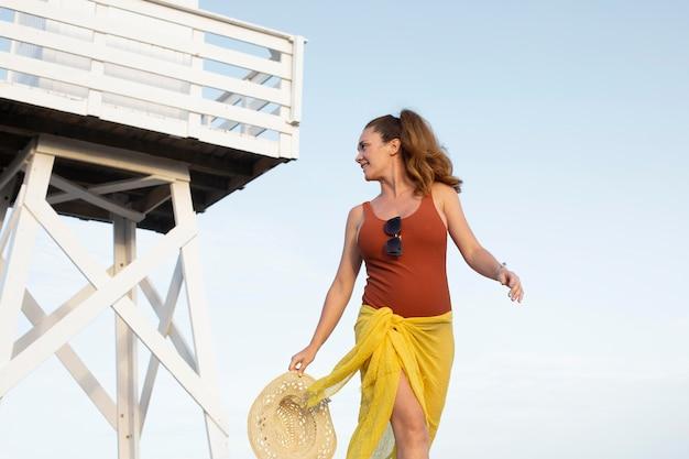 Donna sorridente di colpo medio in spiaggia