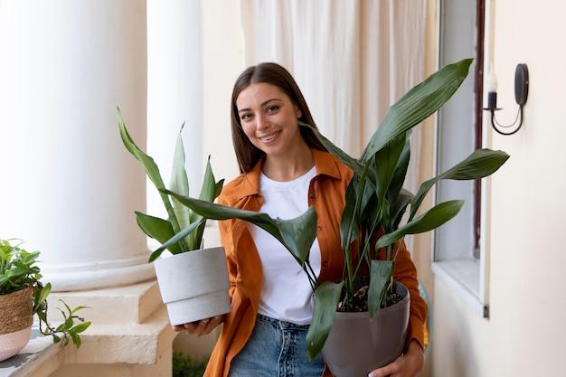 Donna sorridente con colpo medio che trasporta piante