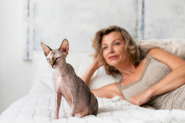 Donna sorridente con colpo medio e gatto a letto