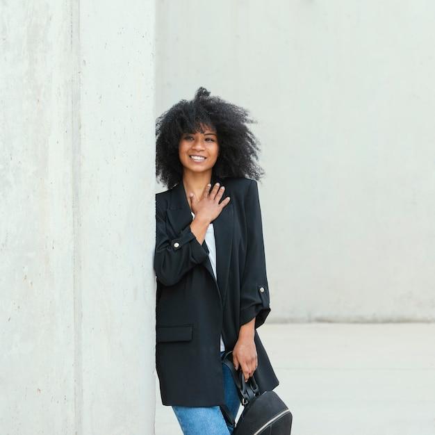 バックパックを保持しているミディアムショットのスマイリー女性