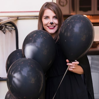 Medium shot smiley woman holding balloons