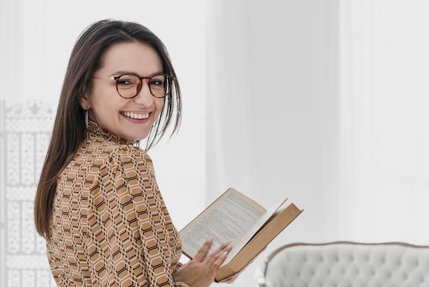 本を持っているミディアムショットスマイリー女性
