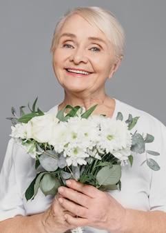 Fiori della holding della donna di smiley del colpo medio