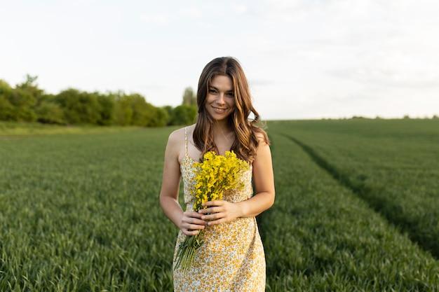 Donna sorridente di colpo medio che tiene i fiori