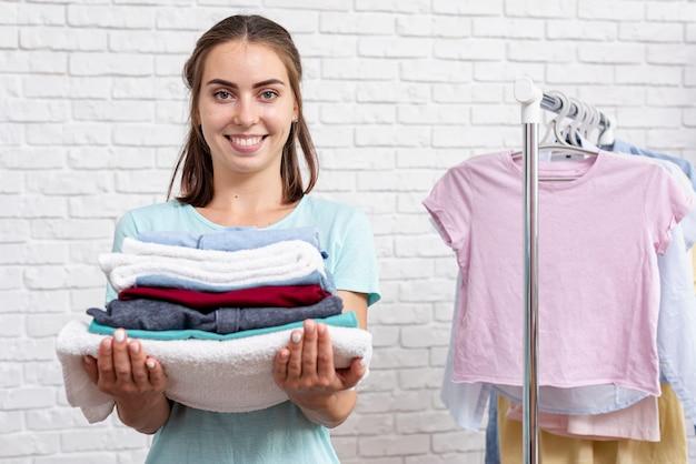 접힌 된 옷과 수건을 들고 중간 샷 웃는 여자