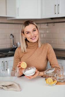 레몬을 들고 중간 샷 웃는 여자