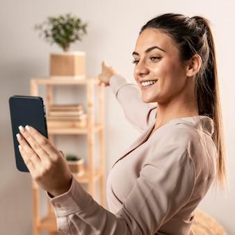 電話を持っているミディアムショットの笑顔の女性