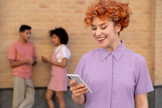 Улыбающаяся женщина среднего выстрела, держащая телефон