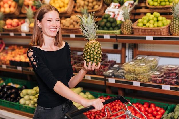 Medium shot smiley woman holding a pineapple