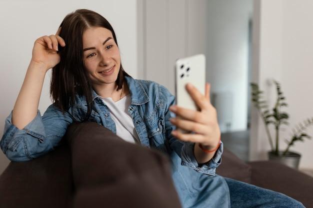 Улыбающаяся женщина среднего выстрела, держащая смартфон