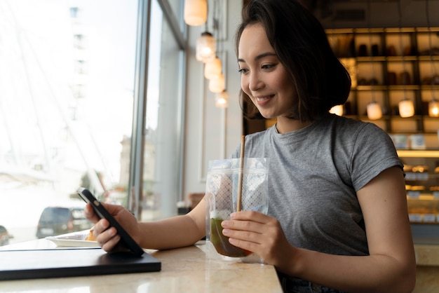 Medium shot smiley woman holding smartphone