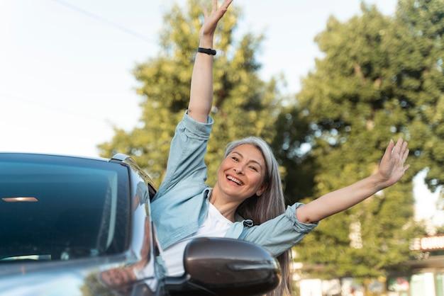 차에 중간 샷 웃는 여자