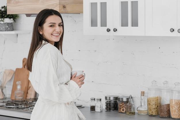 キッチンでミディアムショットの笑顔の女性