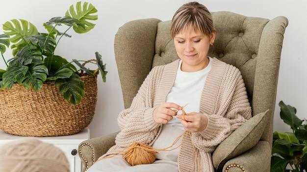 ミディアムショットの笑顔の女性の編み物