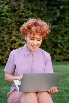 Medium shot smiley woman on laptop