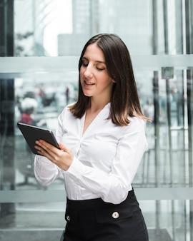 Medium shot smiley woman looking at her tablet