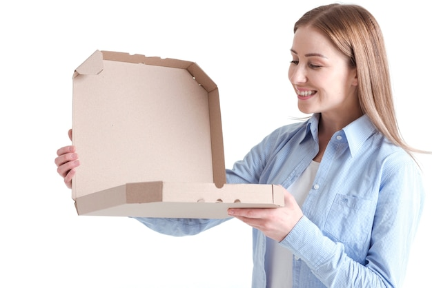 Medium shot of smiley woman looking into a pizza box