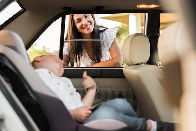 Donna di smiley del colpo medio che esamina il bambino