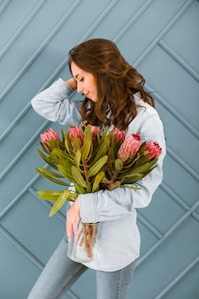 Medium shot smiley woman posing with bouquet