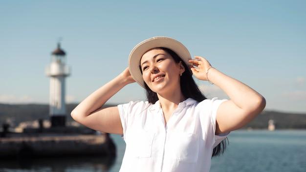 Улыбающаяся женщина среднего выстрела позирует в шляпе