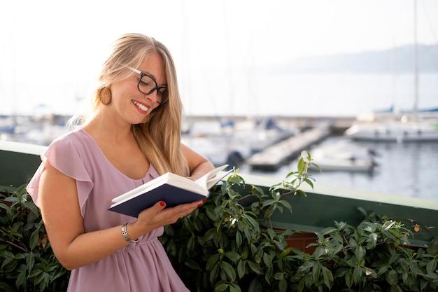 Улыбающаяся женщина среднего выстрела, читающая книгу