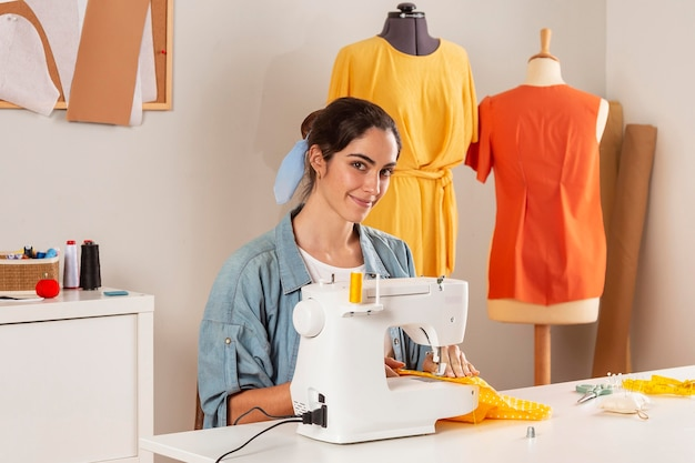 Medium shot smiley woman  sewing with machine