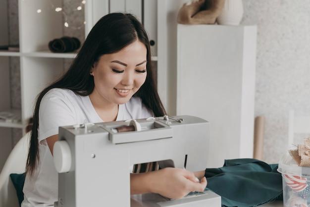중간 샷 웃는 여자 바느질