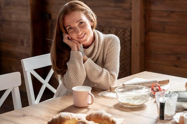 중간 샷 웃는 여자 테이블에 앉아