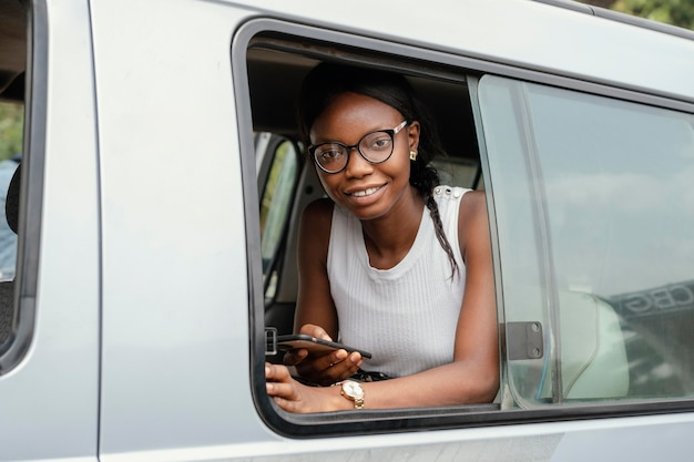 Donna di smiley del colpo medio che si siede in macchina