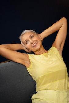 Donna sorridente di colpo medio che si siede sulla sedia