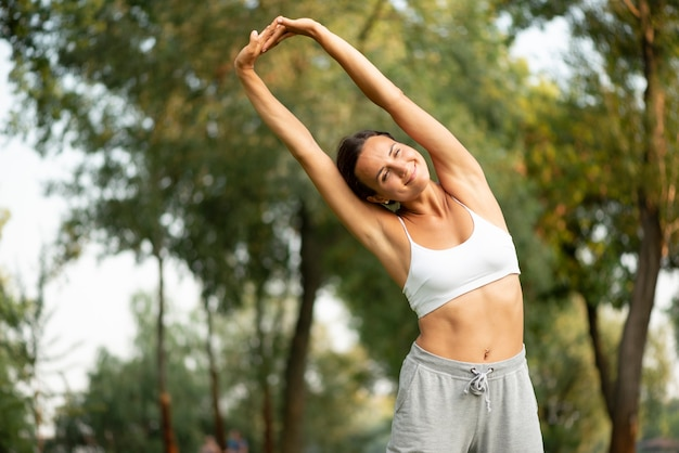 Medium shot smiley woman stretching her body