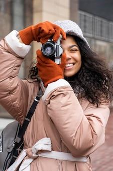 Улыбающаяся женщина среднего кадра фотографирует