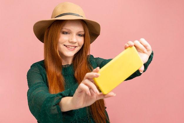 Средний снимок смайлик женщина берет селфи