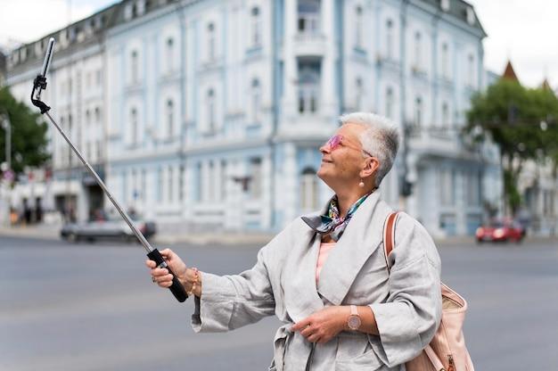 ミディアムショットの笑顔の女性が自撮り