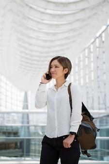 Улыбающаяся женщина среднего выстрела разговаривает по телефону