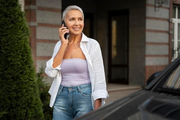 Donna sorridente di colpo medio che parla al telefono