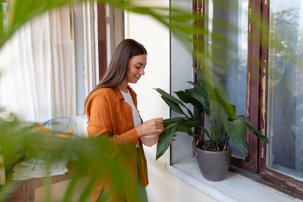 중간 샷 웃는 여자 물을 식물