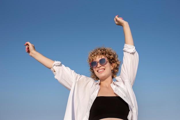 サングラスをかけているミディアムショットの笑顔の女性