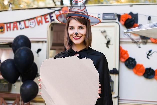 魔女の帽子をかぶっているミディアムショットのスマイリー女性