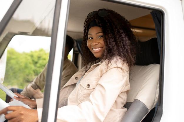 Donna sorridente al volante a tiro medio