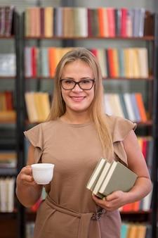 本とミディアムショットのスマイリー女性